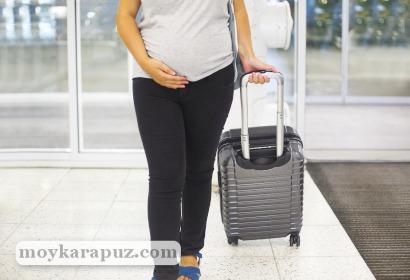 Беременная с чемоданом в аэропорту
