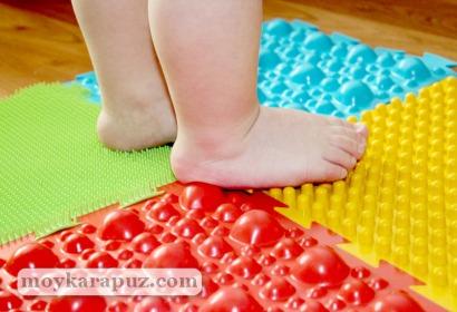 Ребенок ходит по лечебному коврику