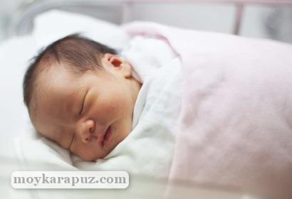 Новорожденный спит в кювезе